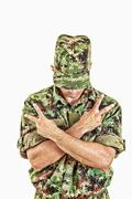 soldier standing with sign of peace with cross arms - stock photo