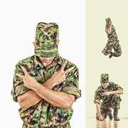 soldier with hidden face in green camouflage uniform jumping and showing peac - stock photo