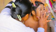 Bagan, myanmar - circa jan 2014: mother gets thanaka to daughter's face Stock Footage