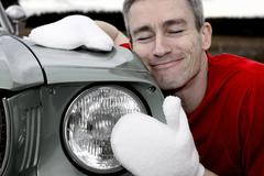 man lovingly caring for his vintage car - stock photo