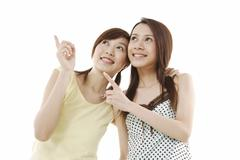 two young asian women pointing and looking at something - stock photo