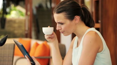 Businesswoman reading news on tablet computer, drinking coffee HD Stock Footage
