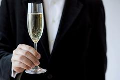 Young man holding a glass of champagne Stock Photos