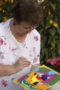 74 year old woman painting with acrylics Stock Photos