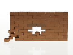 brick wall with a hole falling apart - stock photo