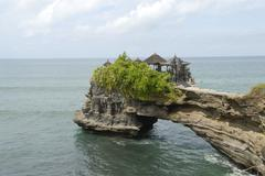 Stock Photo of balinese hinduism, rocky island with a rock arch to the mainland, side temple