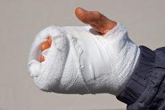 Recently operated hand, bandaged after an accident at work, skin reddish-oran Stock Photos