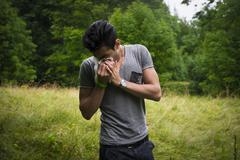 Young man outdoors sneezing in handkerchief Stock Photos