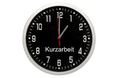 black clock, writing kurzarbeit, german for short-time work, symbolic image - stock photo