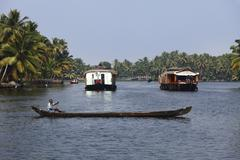 man in a longboat and houseboats, backwater near alleppey, alappuzha, kerala, - stock photo