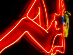 Neon sign in a red light district, nude female Stock Photos