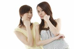 Two young asian women holding their chins Stock Photos