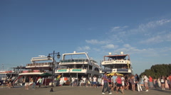 Tourists waiting to board the ships anchored in the harbor for traveling with. - stock footage