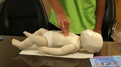 Close up side view practicing CPR on baby Stock Footage