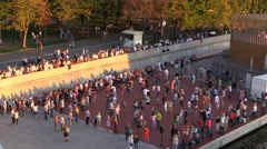 Crowd of people dance on a summer evening river city waterfront Stock Footage