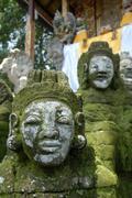 Bali hinduism, old faces on moss-covered stone statues, pura griya sakti temp Stock Photos