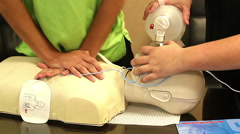 Closeup of 2 people practicing CPR on a dummy Stock Footage