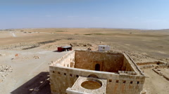 Aerial, drone footage of a small stone building in the eastern desert of Jordan. Stock Footage