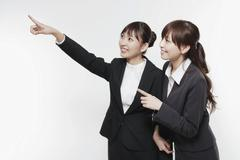 two young asian business women pointing and looking at something - stock photo