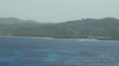 Pan of Honduran coast - airplane in sky Stock Footage