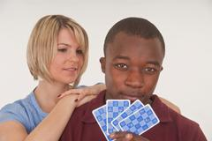 Stock Photo of dark-skinned young man and young european woman playing cards