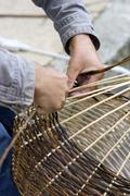 A basket weaver sitting on the street and weaving a basket, brittany, france, Stock Photos