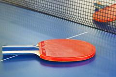 two red tennis racket on ping pong table - stock photo