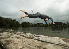 Triathlete diving into Aichstruter Reservoir Welzheim Baden Wurttemberg - stock photo