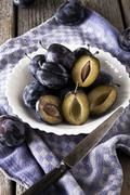 Fresh plums Prunus domestica on plate with a knife and a kitchen towel Stock Photos