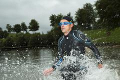 Triathlete running through water Aichstruter Reservoir Welzheim - stock photo