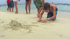 Two young boys building sand castle on beach Stock Footage