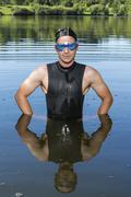 Triathlete standing in Aichstruter Reservoir Welzheim Baden Wurttemberg - stock photo