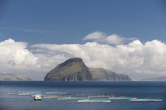 Fish farm clouds and sea in front of the smallest inhabited island of the Faroe Stock Photos