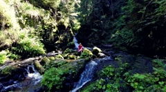 Stock Video Footage of young woman resting by a waterfall