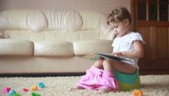Toddler girl sitting on a potty and reading Stock Footage