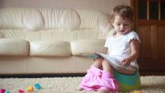 Clever little girl sitting on a potty and reading book. Stock Footage