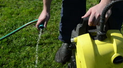 Man hand detach water hose to high pressure wash equipment Stock Footage