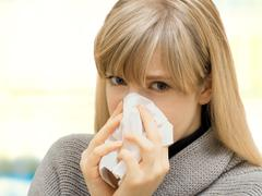 Young woman using a tissue, blowing her nose, sick, allergy Stock Photos