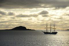 Ship sailing past an island at sunset Insel Havsteinen Alesund More og Romsdal Stock Photos