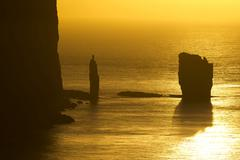 Kellingin and Risin sea stacks petrified trolls according to legend at sunset Stock Photos