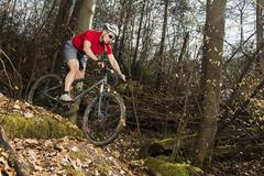 Cyclist on a mountainbike riding through a forest Schurwald forest Winterbach - stock photo