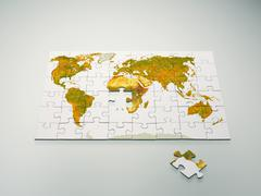 Puzzle with world map single puzzle piece lying apart - stock photo