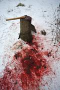 Home slaughtering on a farm chopping block and axe in the snow duck - stock photo