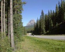 Castle Mountain, Bow Valley Parkway + motorcycle approaches + tilt up Stock Footage