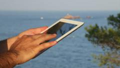 Stock Video Footage of Browsing tablet Next to the Seashore Rack Focus