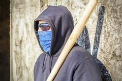 Man with a baseball bat at old wall background - stock photo