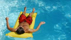 Man relaxing on swimming pool raft floating on water Stock Footage