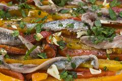anchovy fillets with capsicum stripes with garlic, olive oil and parsley - stock photo