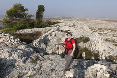hiking woman with backpack in smokvica, pag island, dalmatia, adriatic sea, c - stock photo
