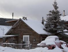 Stock Photo of old log house and old snow covered truck near lake bennett, carcross, yukon t